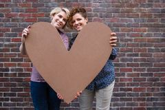 Young lesbian couple smiling contently while holding a heart outside. Portrait of a smiling young lesbian couple standing outside together in front of a brick royalty free stock photo