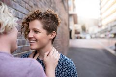 Young lesbian couple standing outside looking into each other`s eyes Stock Images