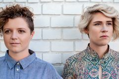 Young lesbian couple standing together outside looking in different directions stock photography