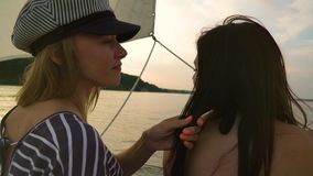 Young lesbian woman touching hair of her partner on sailboat at sunset. Young people on vacation. lgbt, gay couple, summer holidays stock video footage