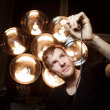Young light designer looking at old electric bulb stock images
