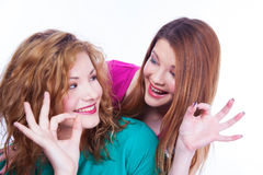 Young lighthearted girls shows Okay gesture Royalty Free Stock Photos