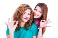 Young lighthearted girls shows Okay gesture Stock Images