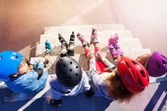 Young in-line skaters sitting on stairs outdoors Stock Photo