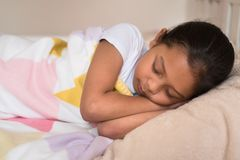 Young little asian girl sleeping lying on bed in her bedroom. Sleep concept Royalty Free Stock Images