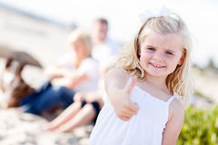 Young Little Blonde Girl Gives Thumbs Up. Adorable Little Blonde Girl with Thumbs Up At the Beach with Her Family Royalty Free Stock Photo