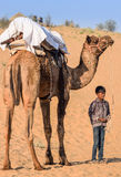 Young little boy with camel in desert at Jodhpur, Ra. Jodhpur, India - December 9, 2014: A little boy, with a frown from bright desert sun, standing holding the Royalty Free Stock Photography