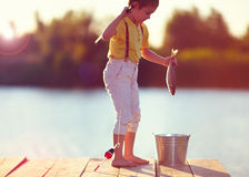 Young little boy caught a fish on the hook, on pond at sunset royalty free stock photo