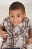 Young little boy in checkered shirt and jeans. Young little boy on bed Royalty Free Stock Photos