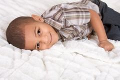 Young little boy in checkered shirt and jeans. Young little boy on bed Royalty Free Stock Image