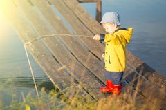 Young little boy fishing from wooden dock.  Royalty Free Stock Image