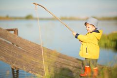 Young little boy fishing from wooden dock.  Stock Image