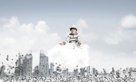 Little boy keeping mind conscious. Young little boy keeping eyes closed and looking concentrated while meditating on cloud among flying letters with cityscape Stock Photo