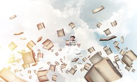 Little boy keeping mind conscious. Young little boy keeping eyes closed and looking concentrated while meditating among flying books in the air with cloudy Stock Images