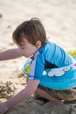 Young little boy playing with the sand and building sandcastle at the beach near the bay. Stock Image