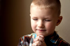 Young little boy praying. Young little boy (child, kid) spiritual peaceful praying and wishing, close up portrait with copy space stock photography