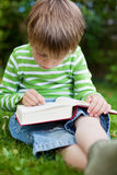 Young little boy reading with finger on book Royalty Free Stock Photography