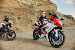 Young little boy sitting on a racing motorcycle, a beautiful little biker on a sports bike in nature. Son of a motorcycle racer. royalty free stock photography