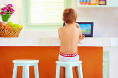 Young little boy watching video through the internet, while sitting in kitchen in the morning Stock Images