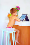 Young little boy watching video through the internet, while sitting in kitchen in the morning Royalty Free Stock Images