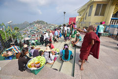 Young little Buddhist monk pointing somewhere afar while pilgrims passing by & vendors selling snacks along the stairs. In the background is a large community Royalty Free Stock Photography