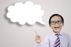 Young little businessman with a cloud bubble. Closeup of young little businessman getting an inspiration while pointing an empty cloud bubble Stock Image