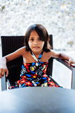 Young little cute girl sitting on the chair alone waiting Stock Photos