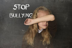Young little cute schoolgirl scared sad covering her face and the words stop bullying text stock photos