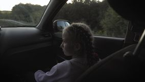 Young little girl enjoying the trip in looking out the window of the car. The girl is looking out the window. Back view. stock footage