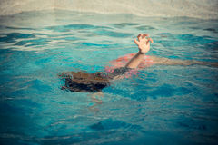 Young little girl floating at swimming pool. And showing hand calling for help when she playing on summer holiday and drowning in water royalty free stock photos