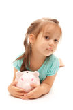 Young little girl holding a piggy bank. On isolated white background Stock Photography