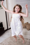 Young little girl jumping. With joy in living room Stock Image