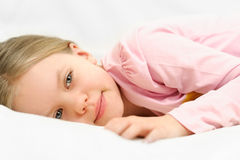 Young little girl is laying on bed with peaceful f Stock Photo