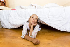 Young little girl lying on floor at bedroom under bed Stock Images