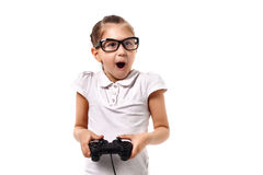 Young little girl play videogame by gamepad. On the white isolated background Royalty Free Stock Images