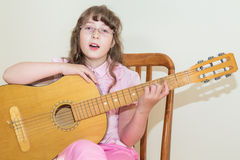 Young little girl playing acoustic guitar Stock Photography