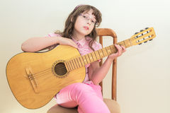 Young little girl playing acoustic guitar Stock Images