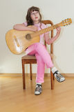 Young little girl playing acoustic guitar Stock Photo