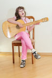 Young little girl playing acoustic guitar Stock Photos