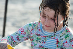 Young little girl playing with the sand and building sandcastle at the beach near the sea. Stock Image