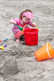 Young little girl playing with the sand and building sandcastle at the beach near the sea. Royalty Free Stock Photos