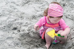 Young little girl playing with the sand and building sandcastle at the beach near the sea. Royalty Free Stock Photo