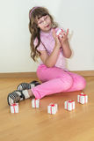 Young little girl playing small giftboxes Royalty Free Stock Images