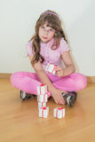 Young little girl playing small giftboxes Stock Image