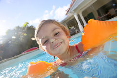 Young little girl playing in the swimming  pool Royalty Free Stock Images