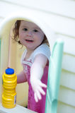 Young little girl playing in toy house in backyard on a sunny day Royalty Free Stock Photography
