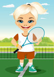 Young little girl with racket and ball on tennis court smiling Royalty Free Stock Images
