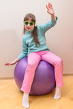 Young little girl sitting on big ball Royalty Free Stock Photos