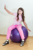 Young little girl sitting on big ball Royalty Free Stock Image