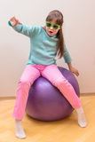 Young little girl sitting on big ball Royalty Free Stock Images